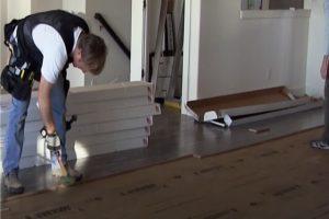 Worker installing dark hardwood floors in a Brampton home.